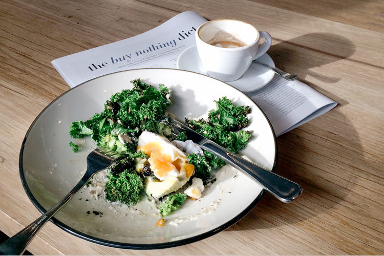 Kale and eggs breakfast on a plate with coffee and the sunday paper magazine