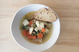 vegetable soup in a bowl with a slice of bread