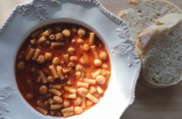 Pasta con ceci in a white bowl and two slices of bread