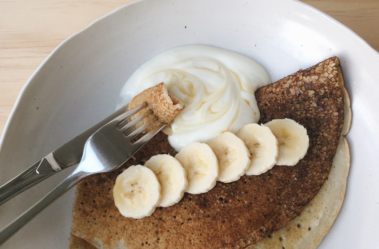 Buckwheat pancakes with yoghurt and banana on a white plate with fork and knife