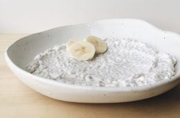 Coconut Chia Pudding in a white shallow bowl with three slices banana.