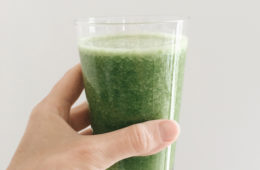 Everyday Kale Smoothie in a glass held up by a hand