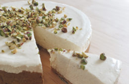 Honey and Cardamom Cheesecake with a piece cut out, on a wooden surface