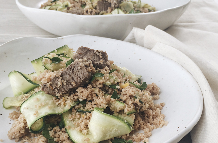 Moroccan Lamb with Lemon Couscous on a white plate with a larger bowl of lamb couscous in the background and a white napkin around