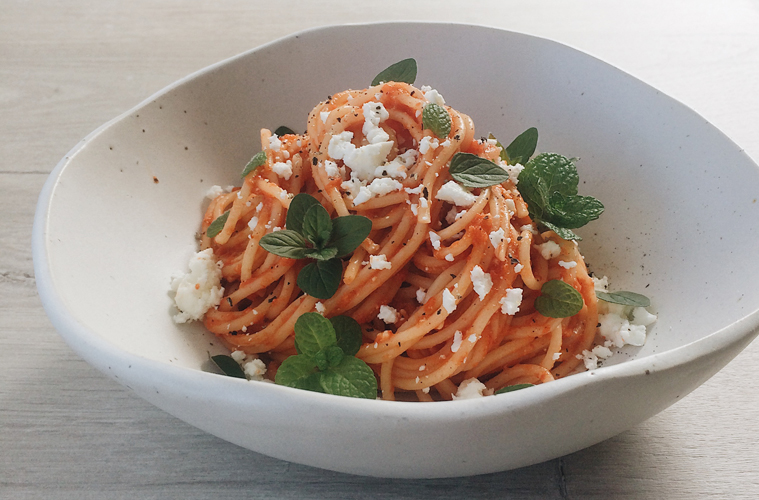 Roast Capsicum, Tomato and Garlic sauce with spaghetti, feta and mint in a white bowl