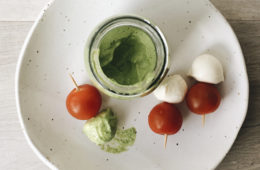 Tahini and Parsley Dressing in a glass jar with three cherry tomato and bocconcini sticks on a white plate