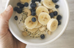 yoghurt, banana, blueberries, hemp seeds, sesame seeds in a white bowl