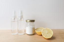 two clear spray bottles, citric acid in a glass jar, a lemon cut in two halves