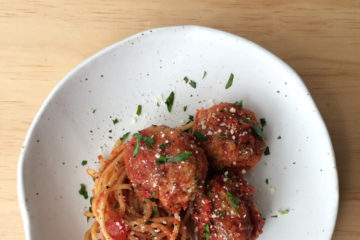 pork meatballs and spaghetti on a white plate with parmesan and parsley sprinkled over