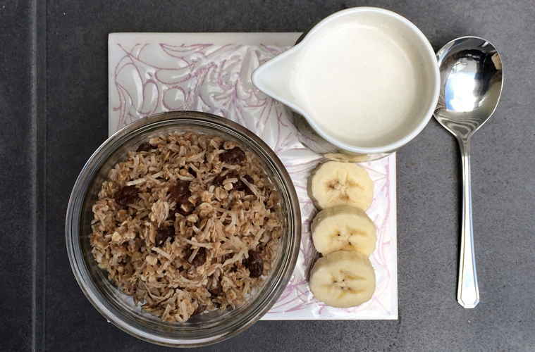 raw muesli in a glass jar with a jug of milk and slices of banana next to it