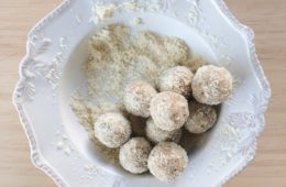 raw lemon truffles rolled in coconut on a white plate