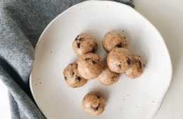 Raw Choc Chip Bites on a white plate with a grey napkin