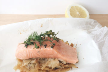 Salmon and Fennel Parcels wrapped in baking paper on a white plate with a piece of lemon in the background