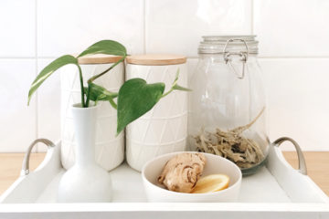 white jars with tea and coffee, a vase with green foliage and a bowl with lemon and ginger on a white wooden tray