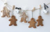 Ginger Bread Men Advent calendar hanging of a string pinned with pegs, with two white bells attached to the string for decoration