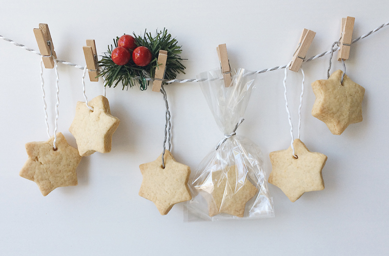 Shortbread stars advent calendar, hanging off a white and grey string, pinned with mini pegs and a green and red christmas decoration