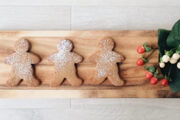 Buckwheat Gingerbread Men on a wooden board with some red and white flowers on the side