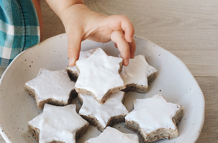 Cinnamon Stars on a white plate with a child's hand reaching for one and picking it up