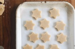 Muerbeteigplaetzchen cut out as stars on a baking tray pre-baking, with some leftover dough next to it on the left hand side