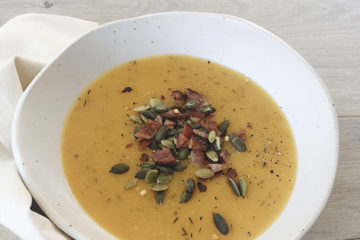Pumpkin soup in a white bowl sprinkled with bacon and pumpkin seeds
