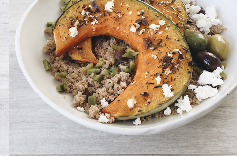 Roasted Pumpkin on Spelt Couscous in a white bowl sprinkled with feta and olives
