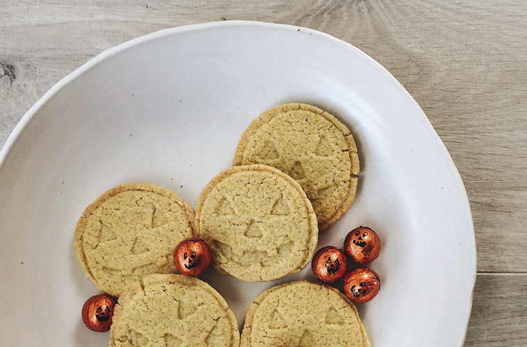 Halloween cookies with chocolate pumpkin balls on a white plate