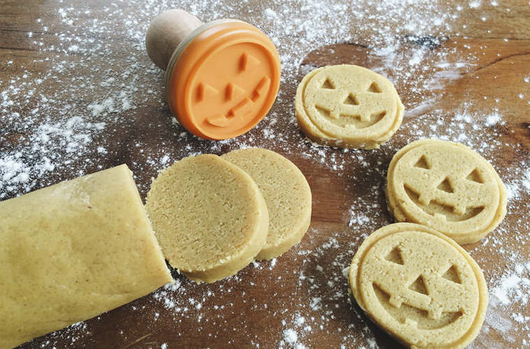 halloween cookies being stamped with a cookie stamp that makes scary pumpkin faces