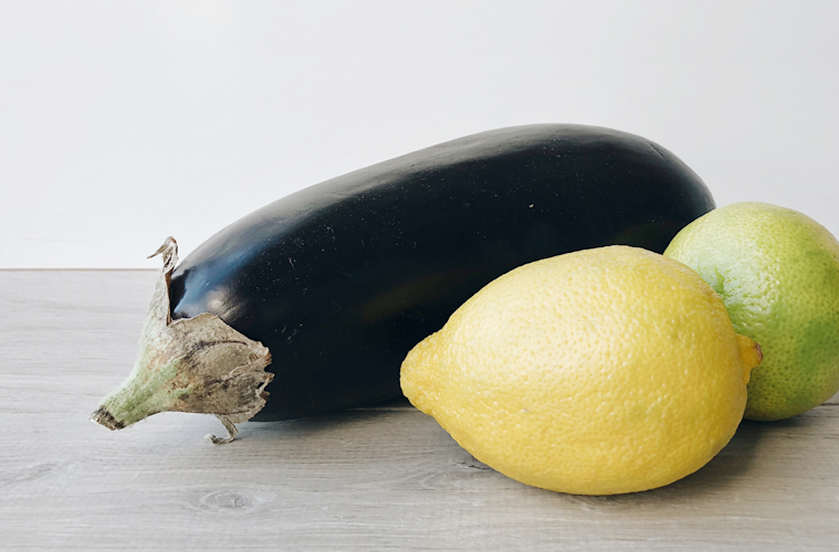 Eggplant, lemon and lime on a wooden surface